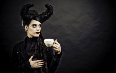 有喝咖啡的垫铁的妇女