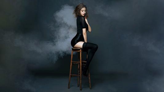 可爱的女孩坐在凳子上