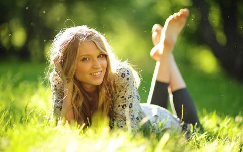 可爱的金发美女在阳光普照的草
