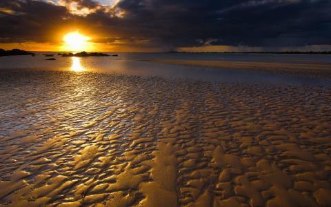 在日落时闪耀的沙滩
